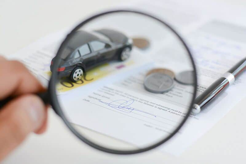 looking at car insurance policy with a magnifying glass