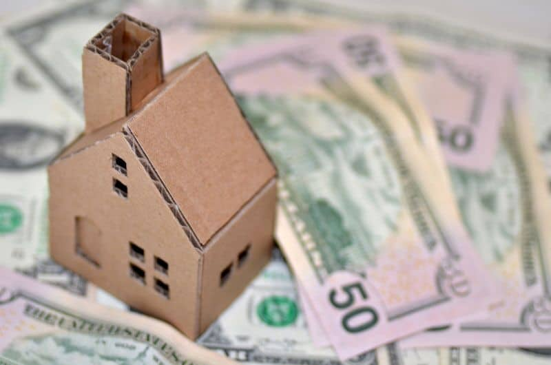 cardboard home on top of cash